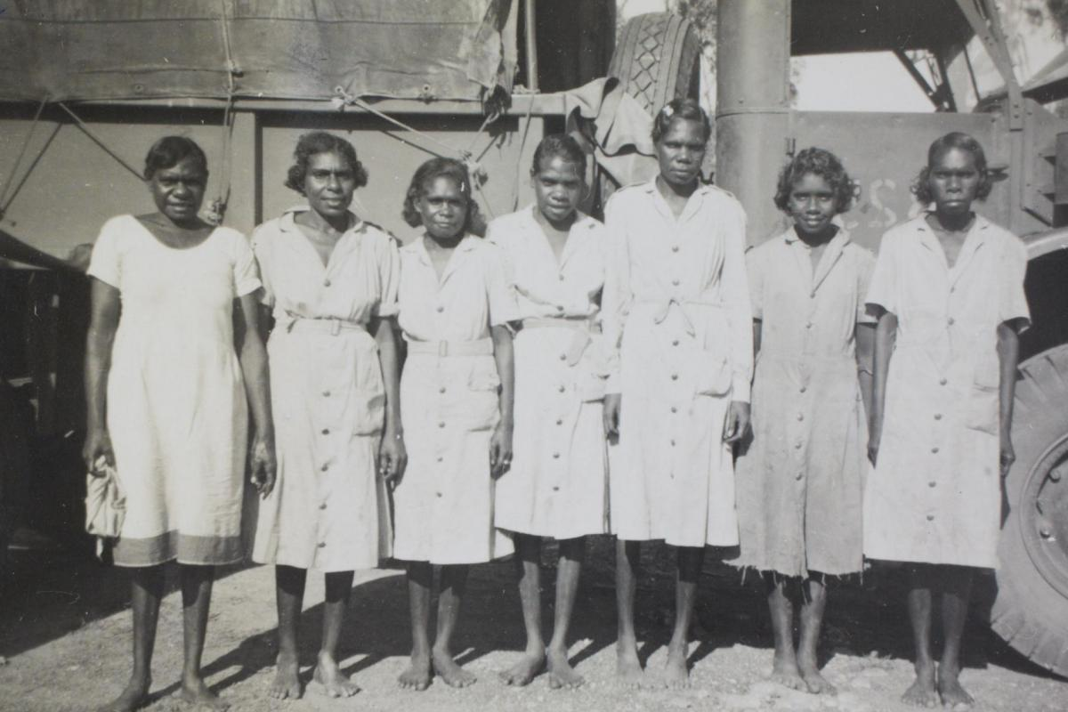 Seven aboriginal women in uniform standing shoulder to shoulder, posing in front of military truck
