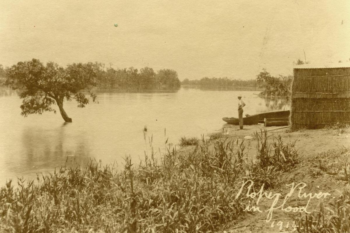 Sepia colour image of man standing on bank and looking at the Roper River with a stack of hay bales behind him