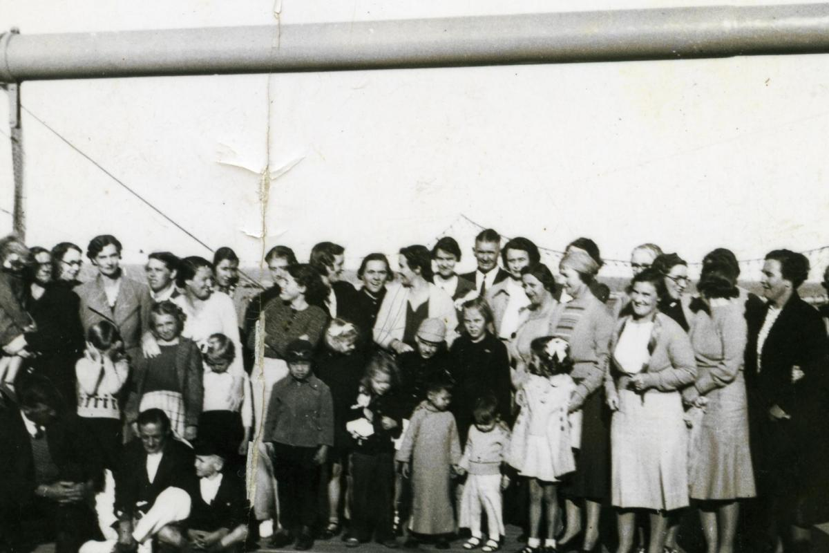 Large group of women and children pose on board ship, possibly prior to evacuation.