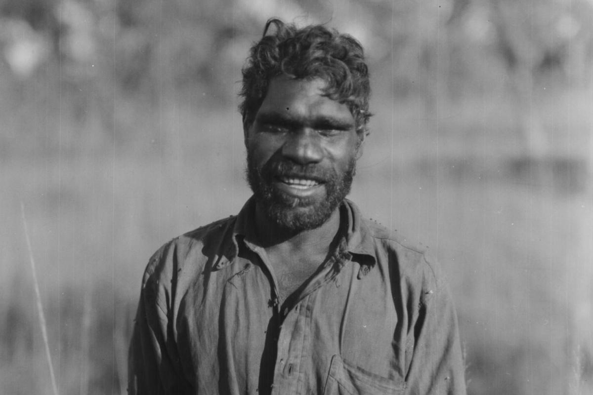 A smiling portrait of Ayaiga in an Australian bush setting.