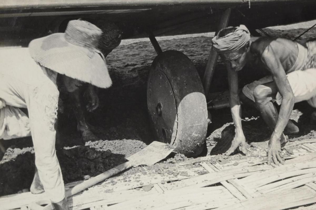 Local villagers lay panels from their bamboo huts underneath the bogged wheels of the Vickers Vimy aircraft in Surabaya, Indonesia, 1919