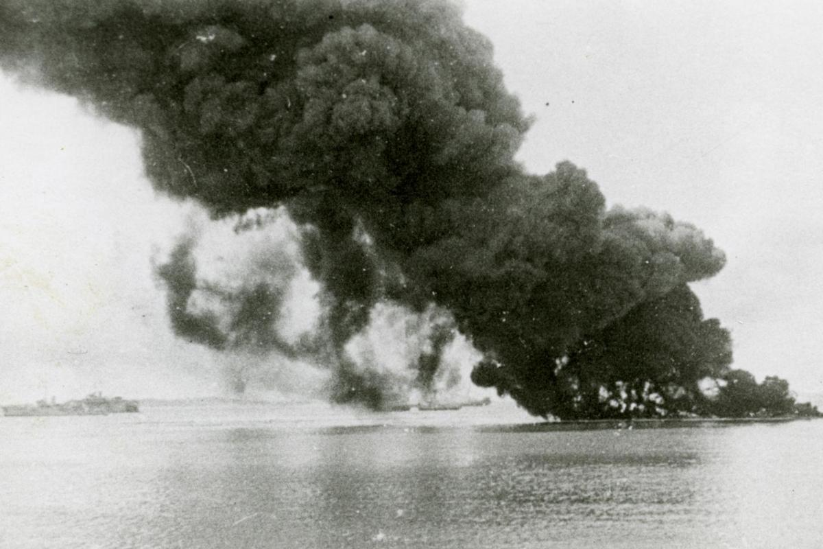 The impact of the first air raid on shipping with (L-R) the HMAS Swan; Floating Dock AFD18; SS Zealandia burning and sinking; HMAS Wato (tug); HMAS Platypus (obscured); oil burning from sunken USS Peary.
