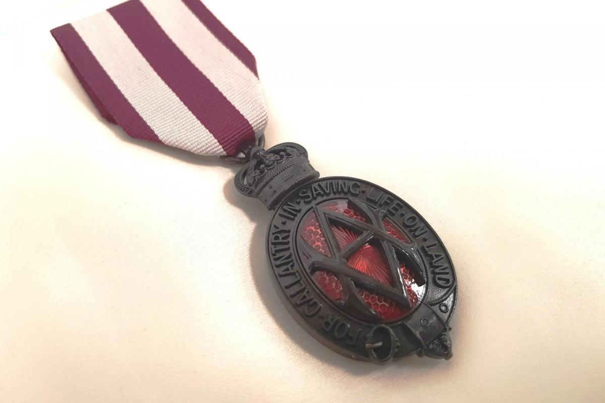 Albert medal. Ribbon is striped maroon and white. Medal is made of bronze with red embelishments