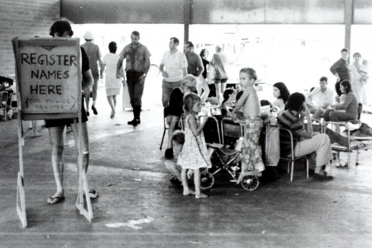 Registration area for evacuees after Cyclone Tracy. Photo shows a registration board and several people waiting around. Casuarina High School