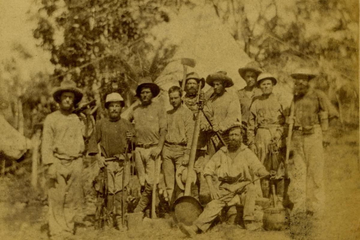 Ten men posing with theodolite and digging tools surveying Darwin 1869