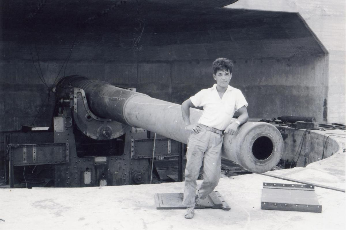 A young member of the Fujita Salvage Company leans against a 9.2-inch counter-bombardment gun at East Point.