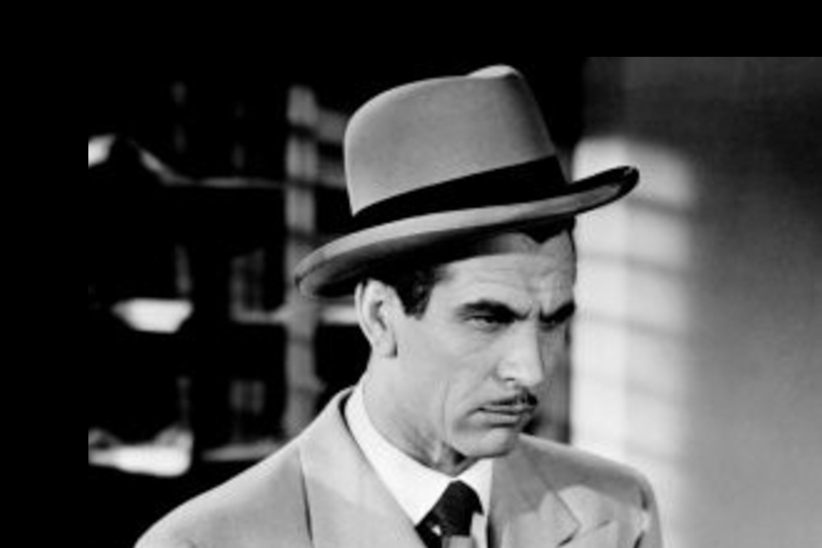A man with a pencil-thin moustache and dressed in a grey suit and homburg inspects a piece of evidence.