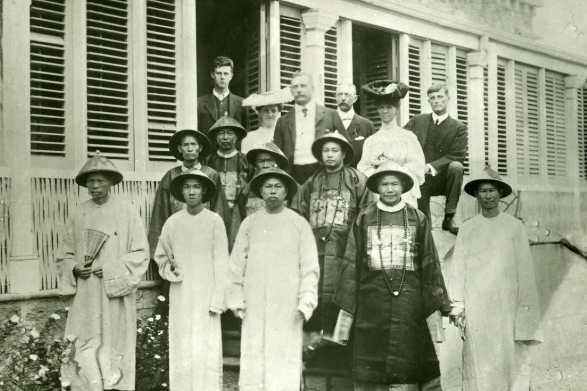 Black and white photo, several people standing in front of a house. Many Chinese merchants dressed in traditional attire.