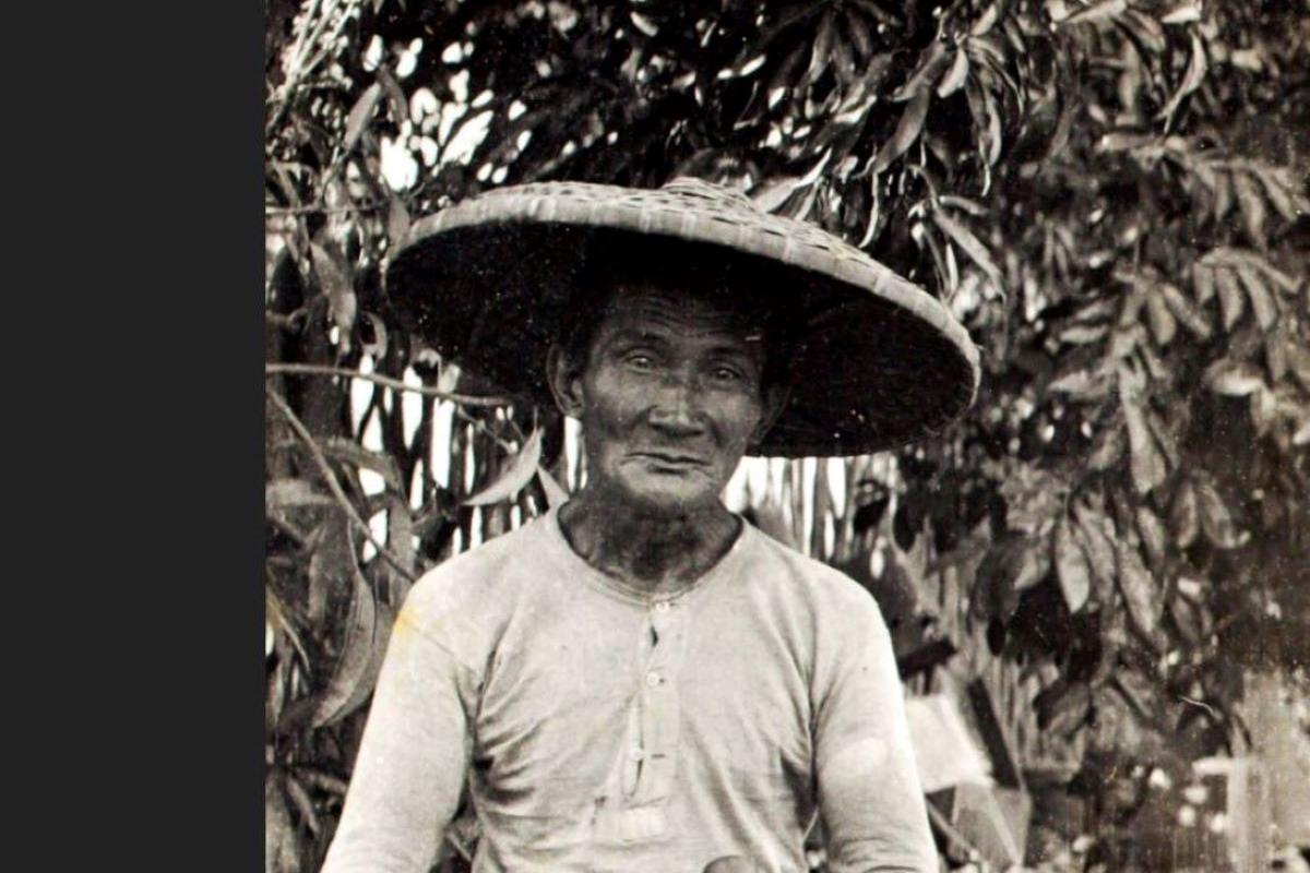 Man wearing a cane hat and sitting on a basket