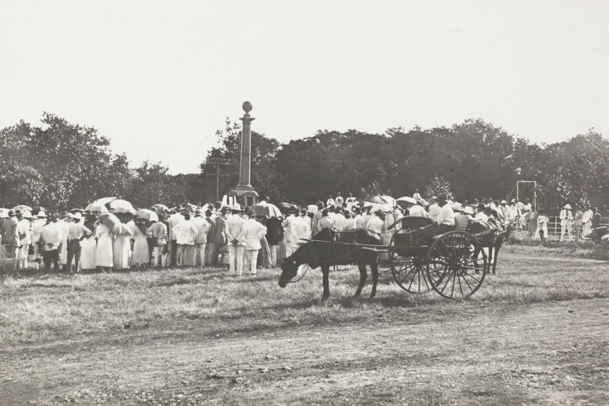 A large crowd of men and women surround the Cenotaph at centre. A horse and buggy stand in the foreground.