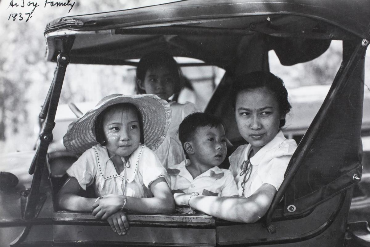 Black and white photo. Two children and a woman sitting in the front seat of an older style car. Women on the seat and two children on leaning on the dashboard. All looking out the passenger side door.