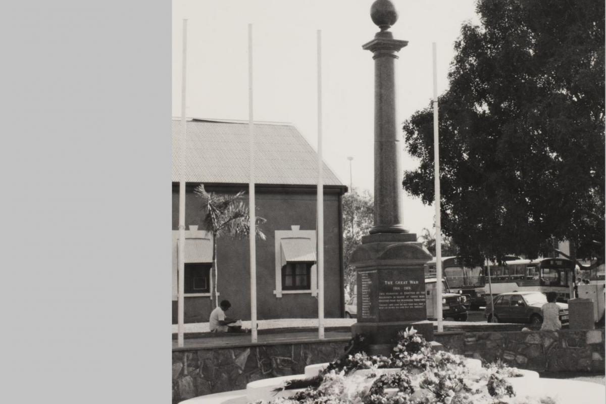 The Cenotaph is at centre with floral wreaths at its base. In the background at left is a building (Browns Mart) and at right is a large tree. A bus can be seen in the far distance.
