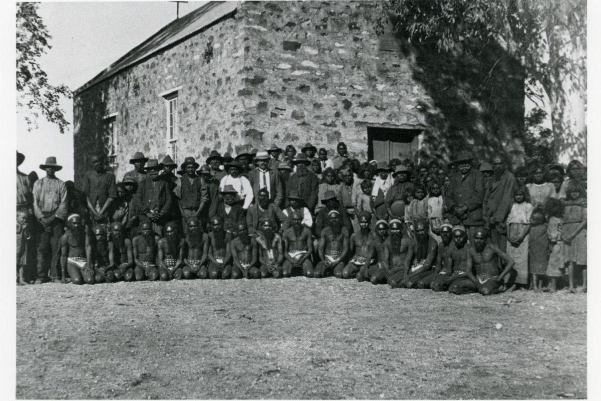 Depicts a large group of Aboriginal people in front of a large stone building.