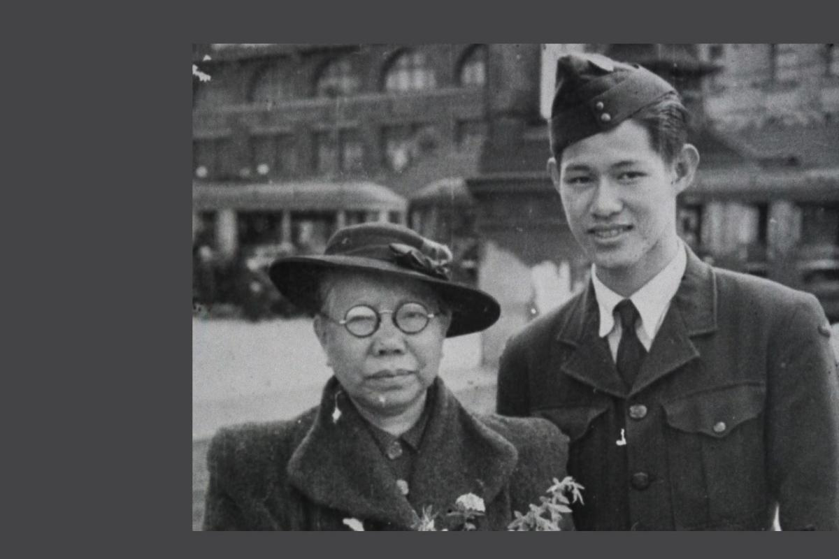 Black and white photo. Young man in RAAF uniform stands next to elderly woman holding a bouquet of flowers.