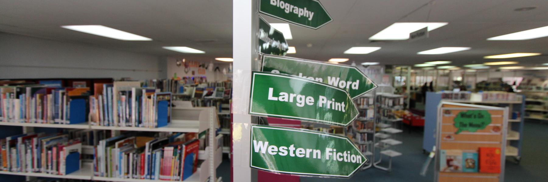 Way finding sign inside a library directing users to different areas of the library resources