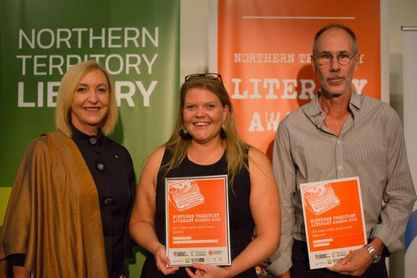 Two women and a man standing side by side. The woman and man on the right are holding orange awards certificates