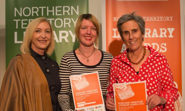 Three women standing side by side. The two women on the right are holding orange awards certificates