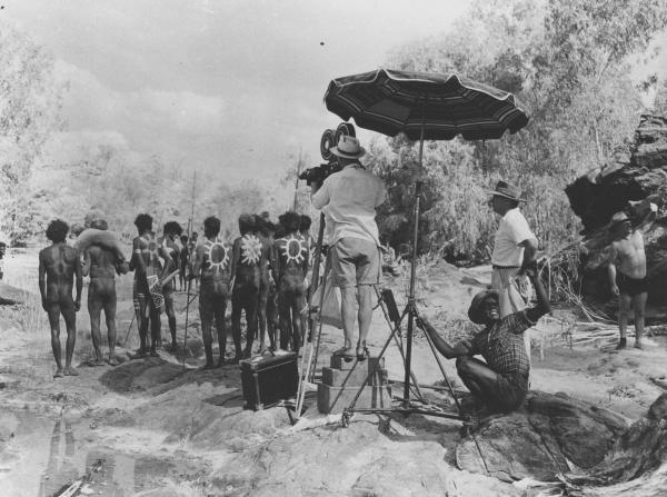 Group of men in Aboriginal traditional dress on film set with a camera crew