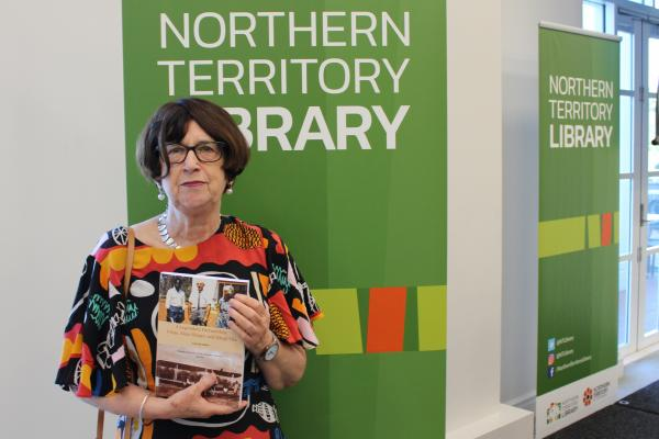 Woman standing in front of green signage, holding a book