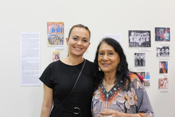 Two women standing in front of exhibition smiling at the camera