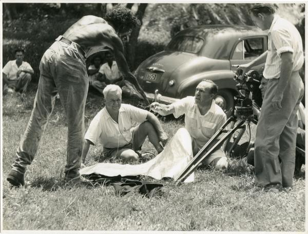 one man standing, leaning over to shake hands with a man sitting in the grass. Another man seated looking out and two other men behind a film camera