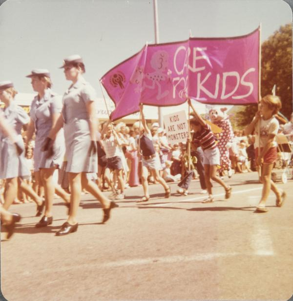 Uniformed nurses walking in a parade followed by children holding a 'care for kids' sign