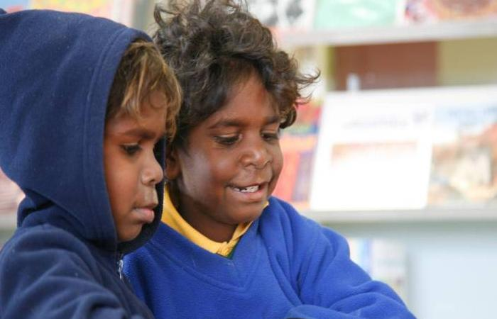 Photo taken inside a library. Two young Aboriginal boys standing at a desk reading a comic book together. Behind is a book display.