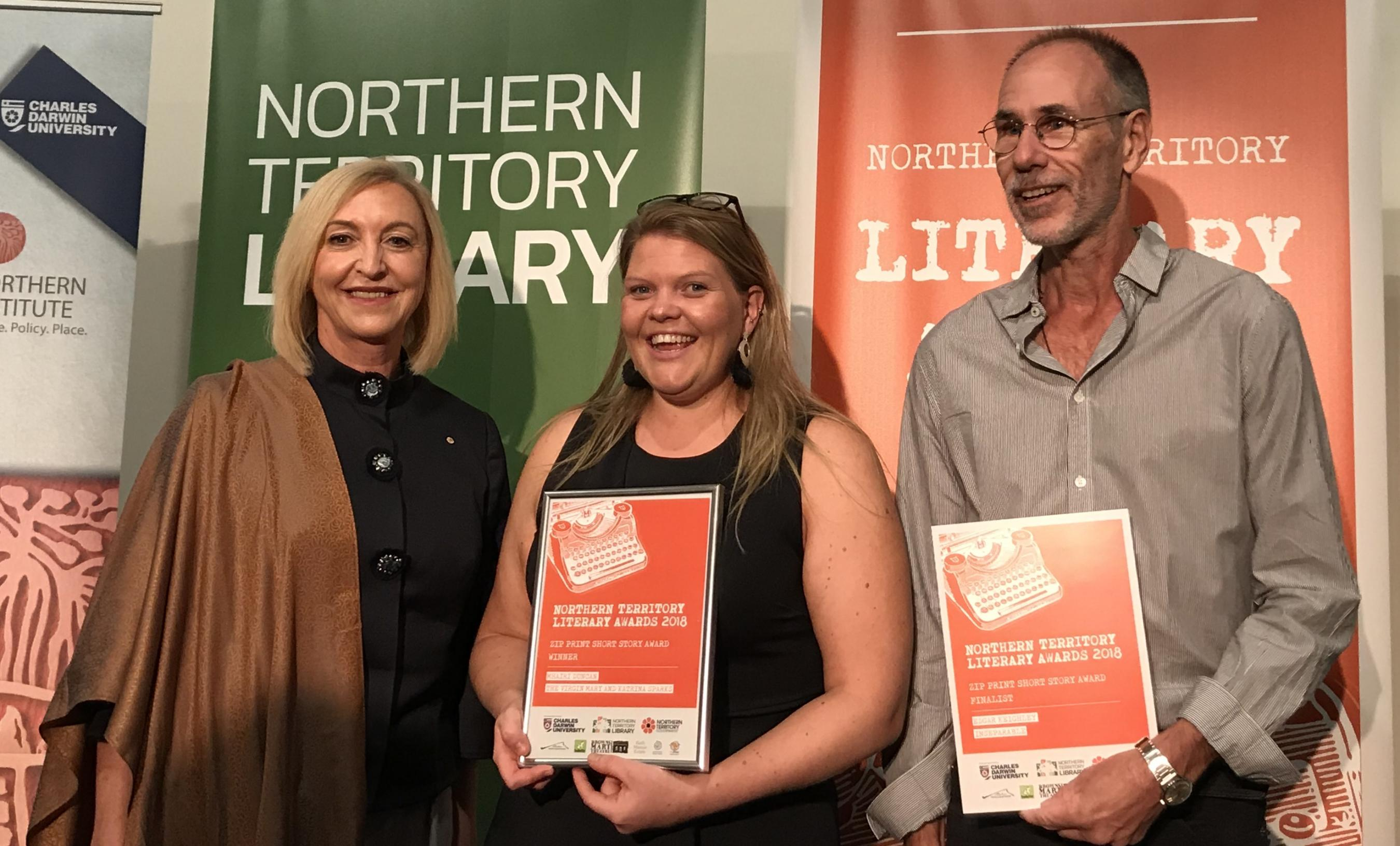 Her Honour the Hounourable Vicki O'Halloran Administrator of the Northern Territory with Mharii Duncan winner of the Short Story Award and Edgar Keighley finalist in the Poetry Award. Event banners in the background.