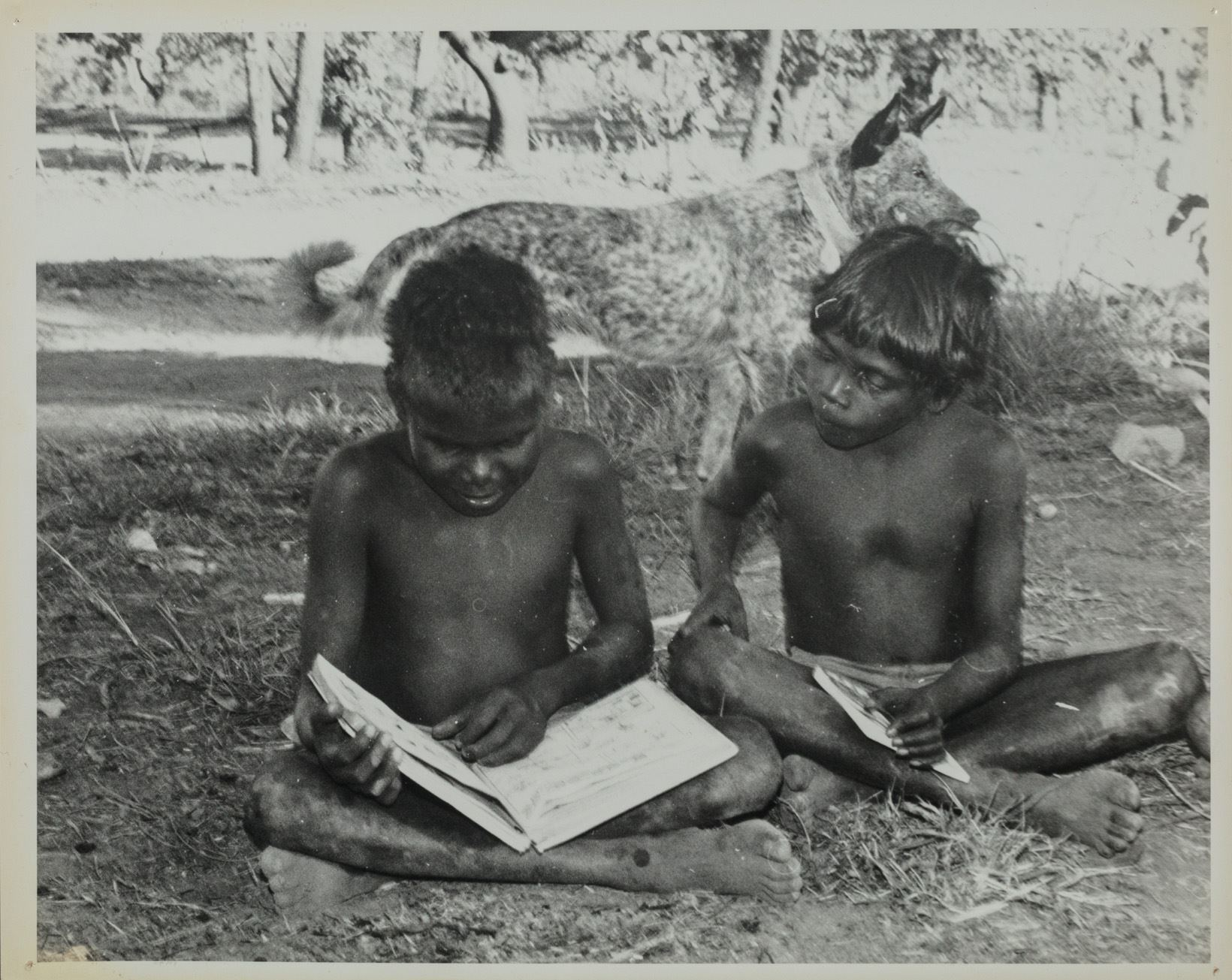 Two young boys with no shirts on sitting crossed legged on the ground reading books