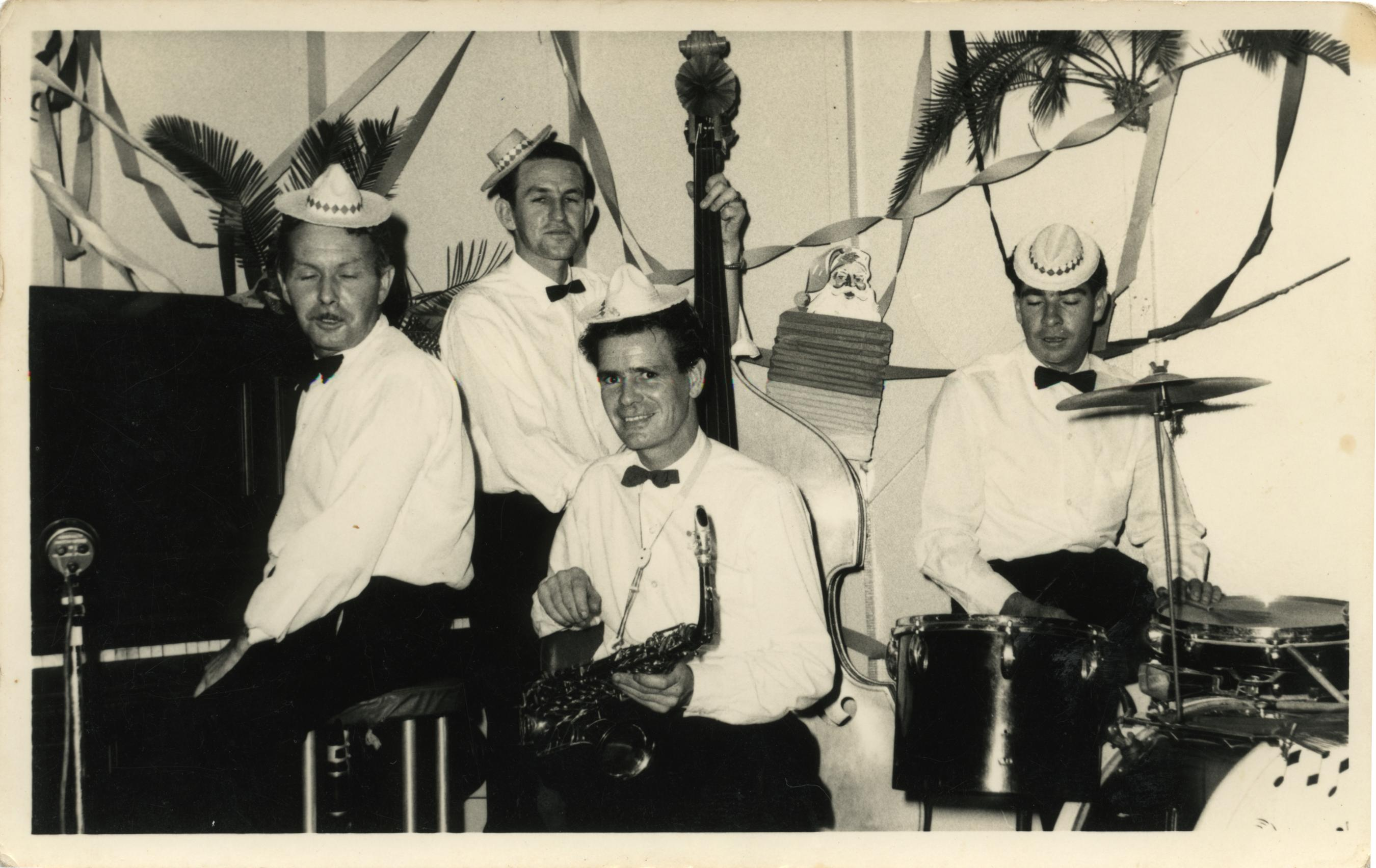 Black and white photo of four men dressing in white shirt and bow ties playing musical instruments. in