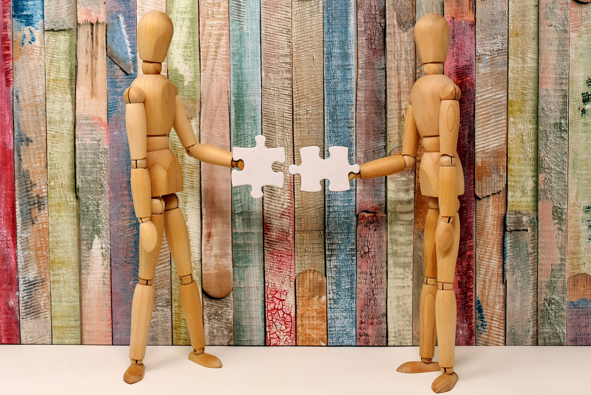 Two wooden drawing models standing in front of coloured panel fencing made of paddle pop sticks each holdig a piece of a puzzle and coming together