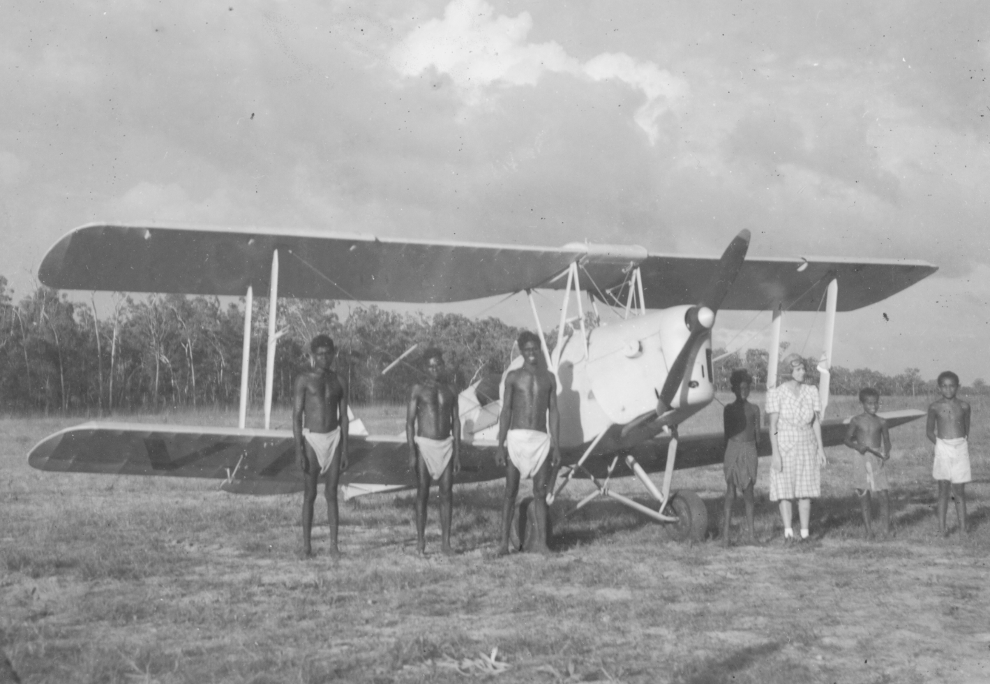 European woman posing alongside six Aboriginal boys in front of a tiger moth aeroplane