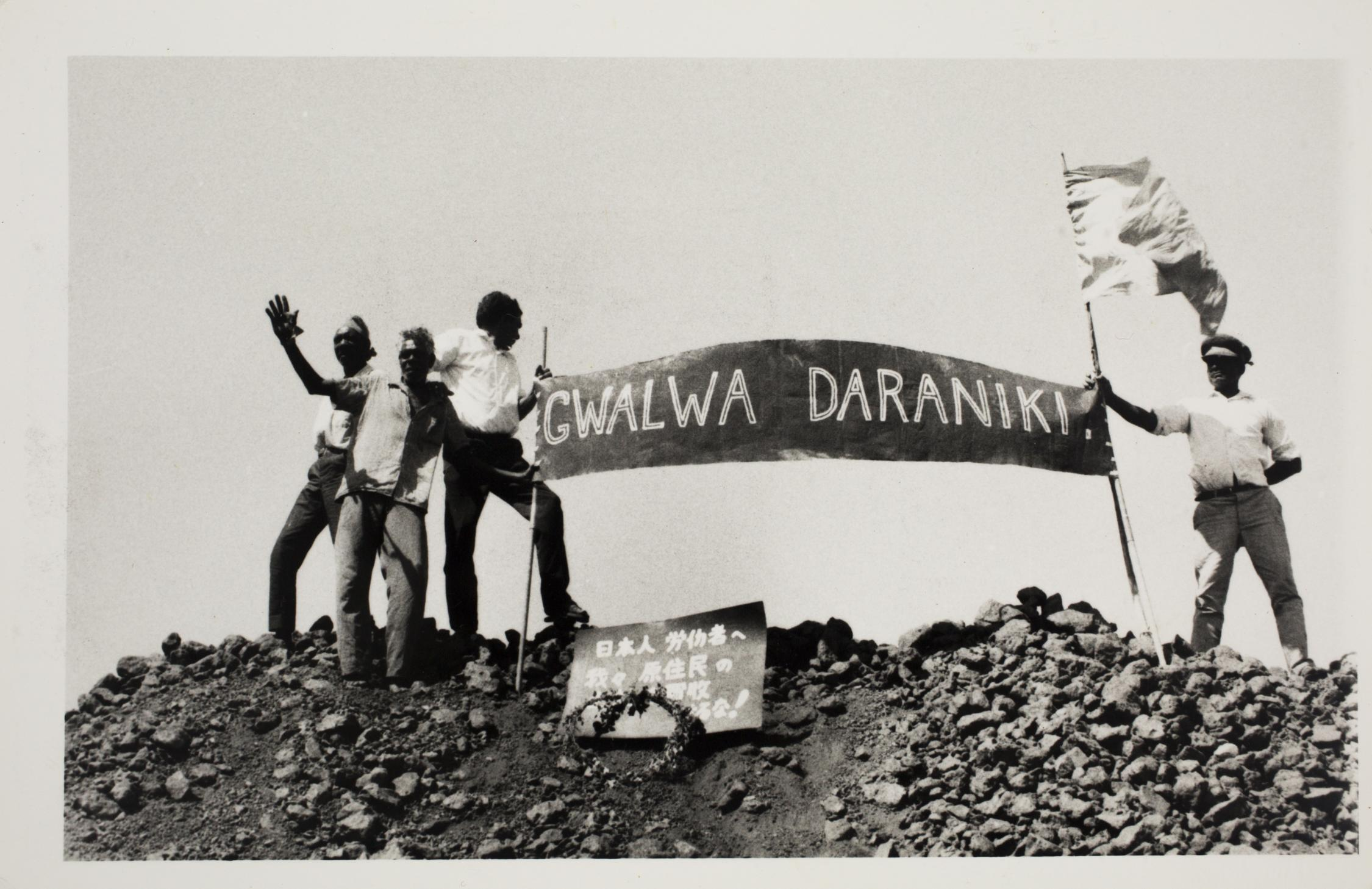 "Four men standing on top a mountain holding a protest sign that reads ""Gwala Daraniki"" meaning ""Our Land"""