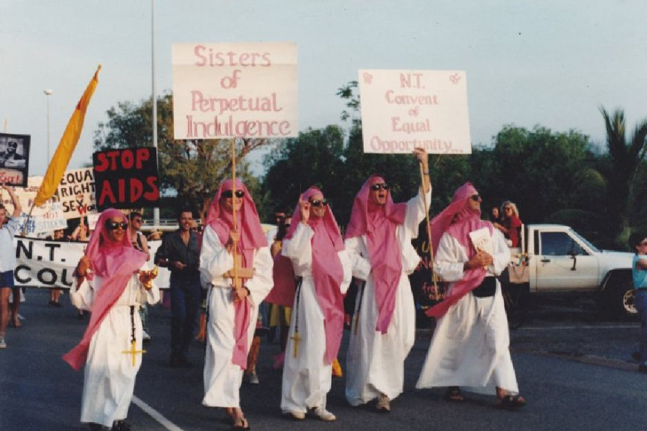 "Five men dressed in white robes and red head scarves marching with placards that reads ""Sisters of Perpetual Indulgence"". March is part of the Gay Pride March in Darwin."