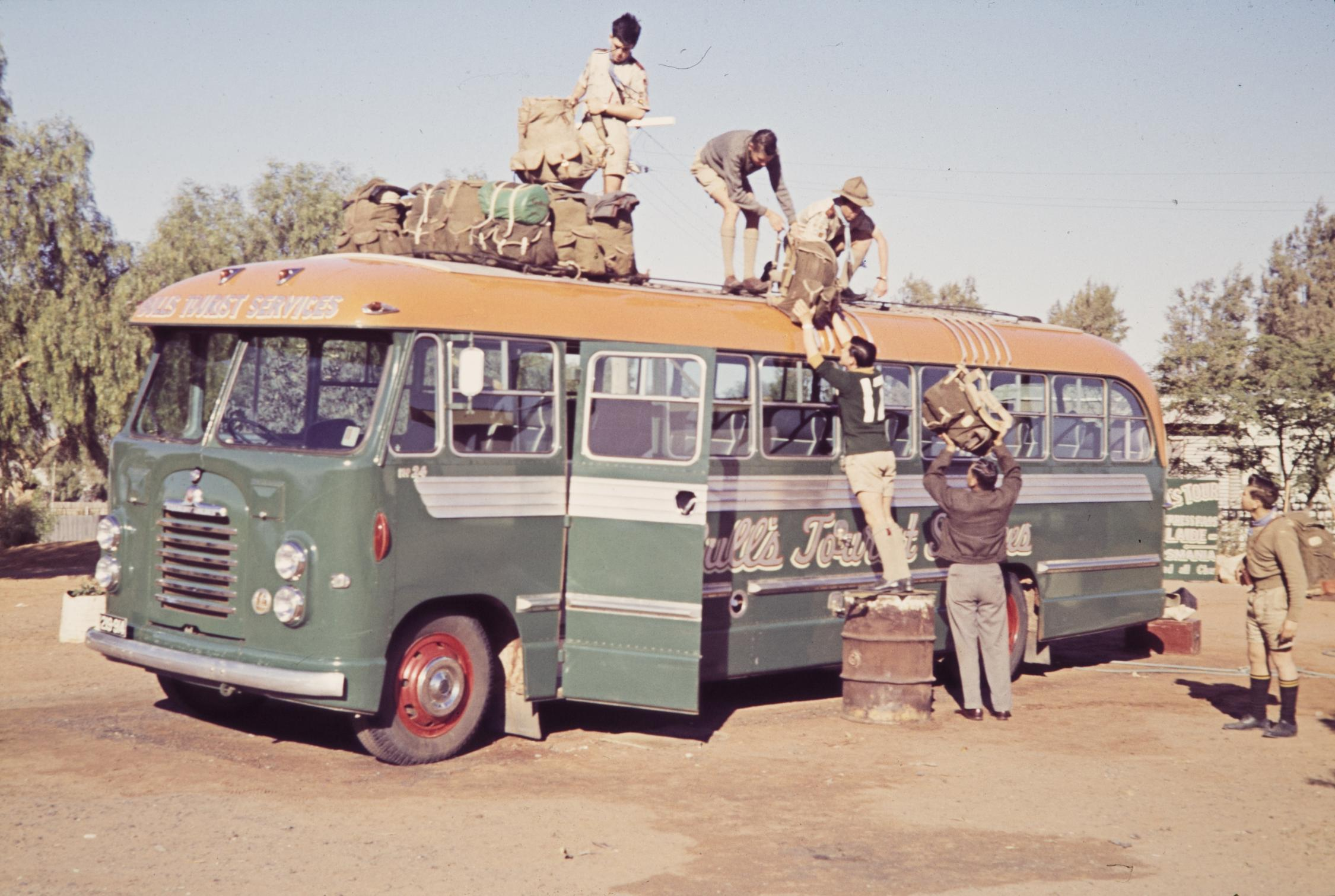 A stationary tour bus from circa 1950s coloured green and yellow being by five boys loading suitcases on the roof of the bus.