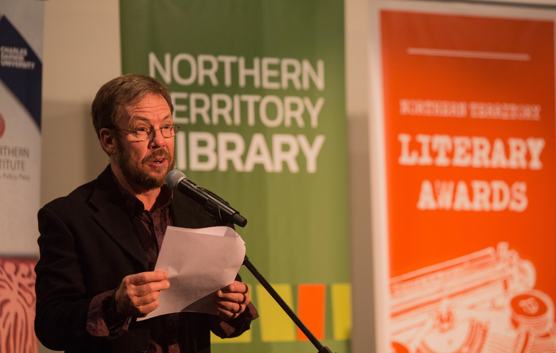 Man on left hand side wearing glass, dark jacket and shirt reading into a microphone. Behind are green and orange banners.