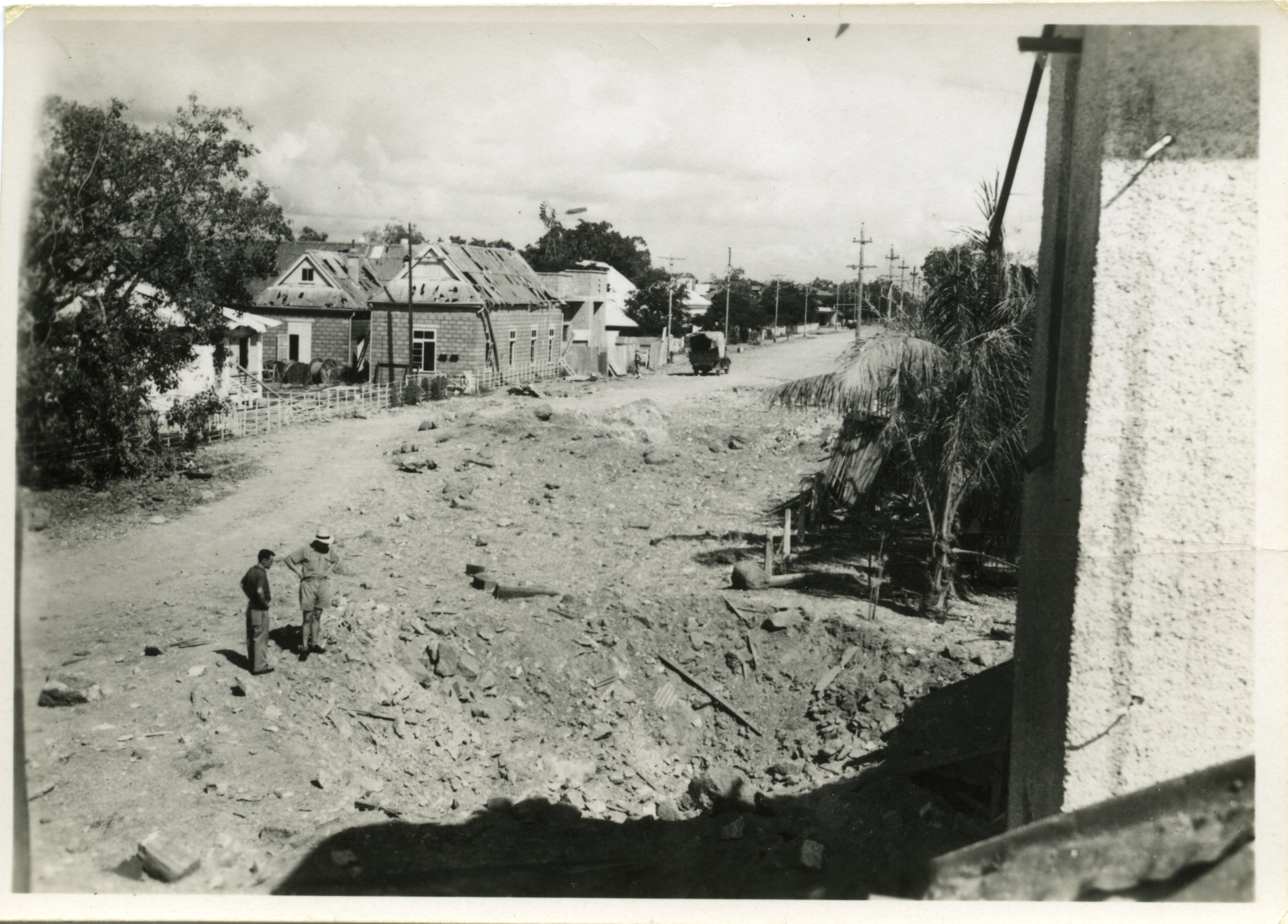Mitchell Street looking away from Port of Darwin, showing bomb damage to the Post Office, including the new Burnett designed extension, and Post and Telegraph and cable precinct. Crater near the Police Barracks. This extensive damage caused by first Japanese bombing on 19/2/1942.