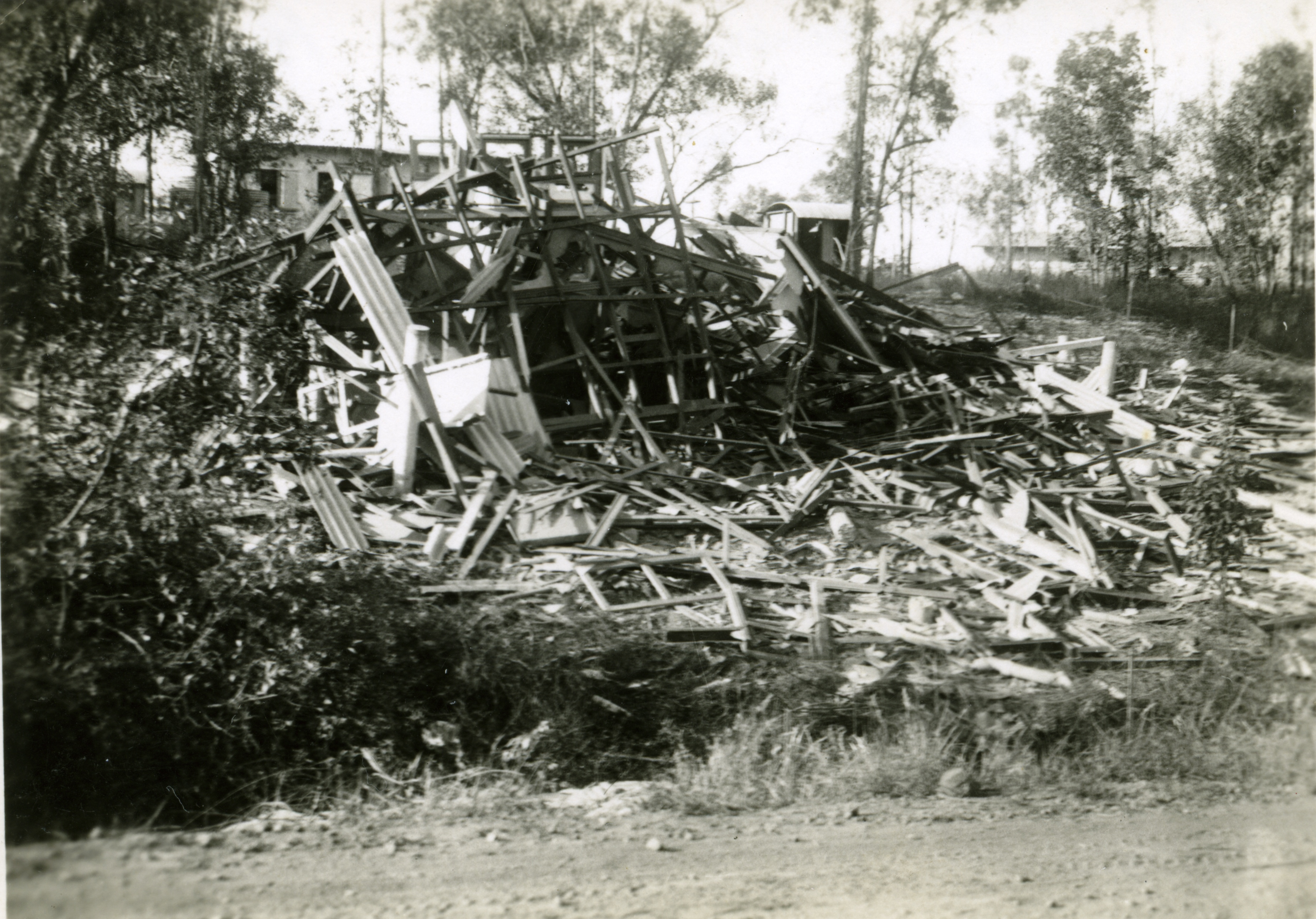 Destroyed house with wooden building materials scattered on the ground.