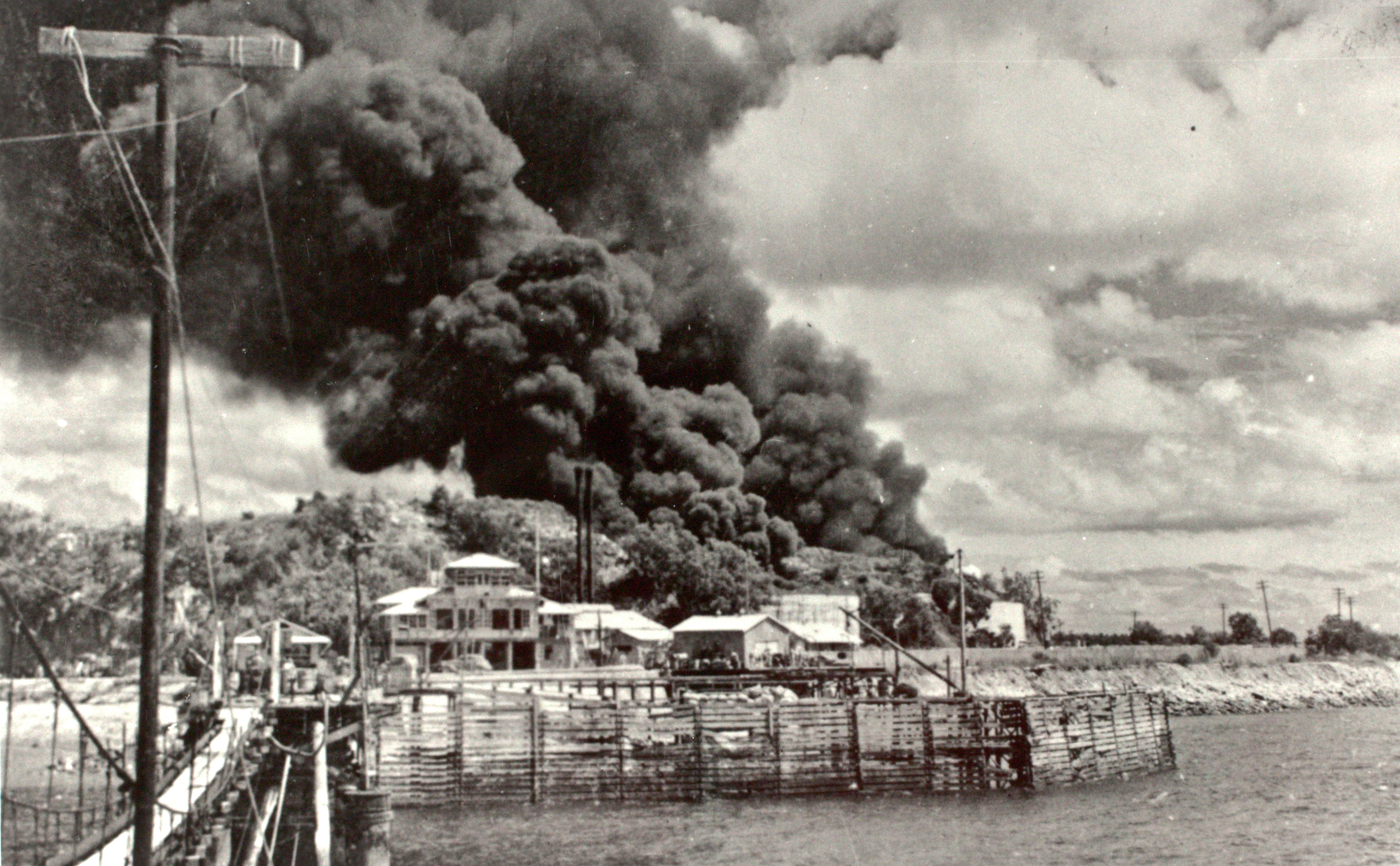 View from Stokes Hill Wharf looking back at burning oil tanks after a bombing raid.