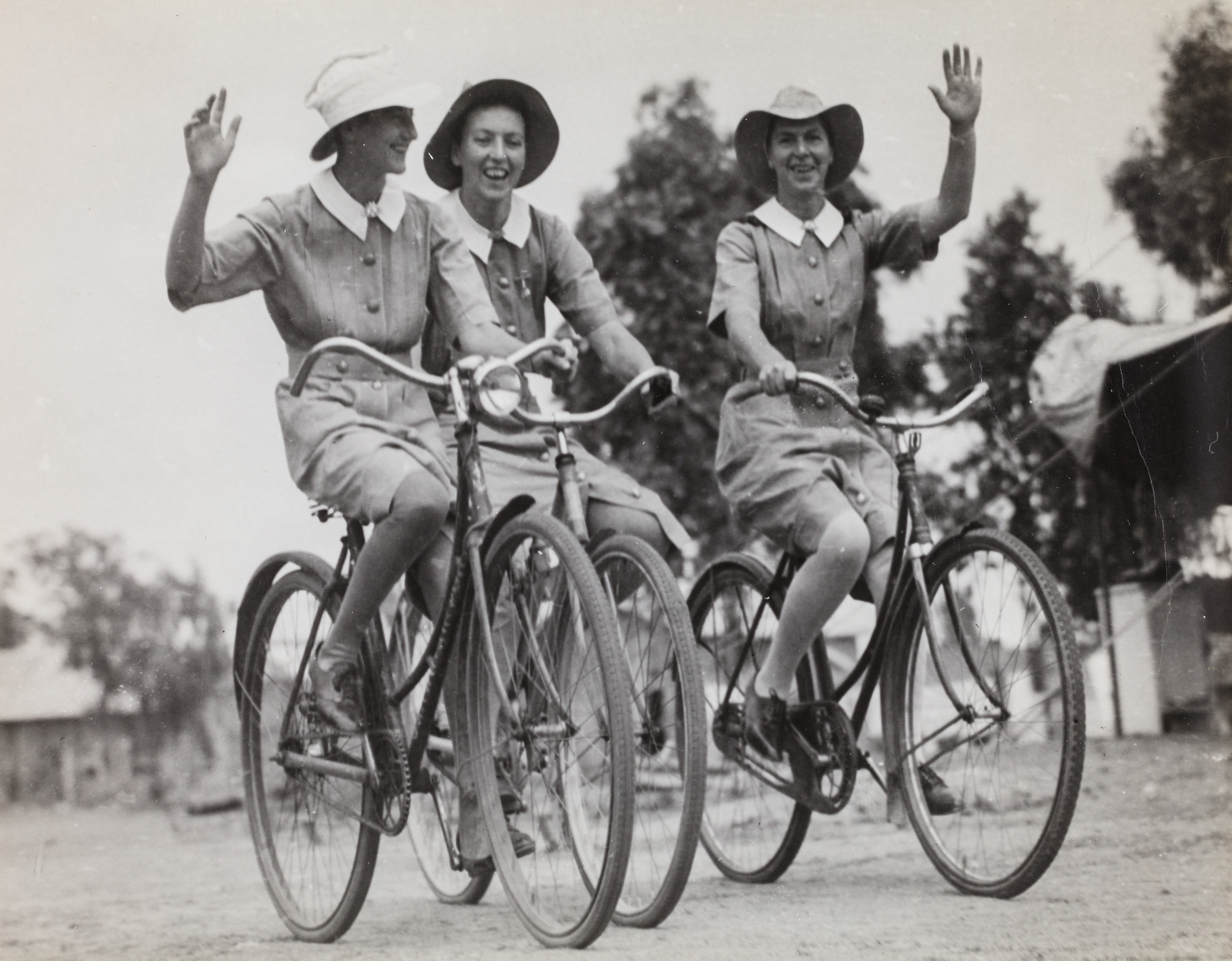 Three nurses in uniform riding bicycles and waving to the camera.