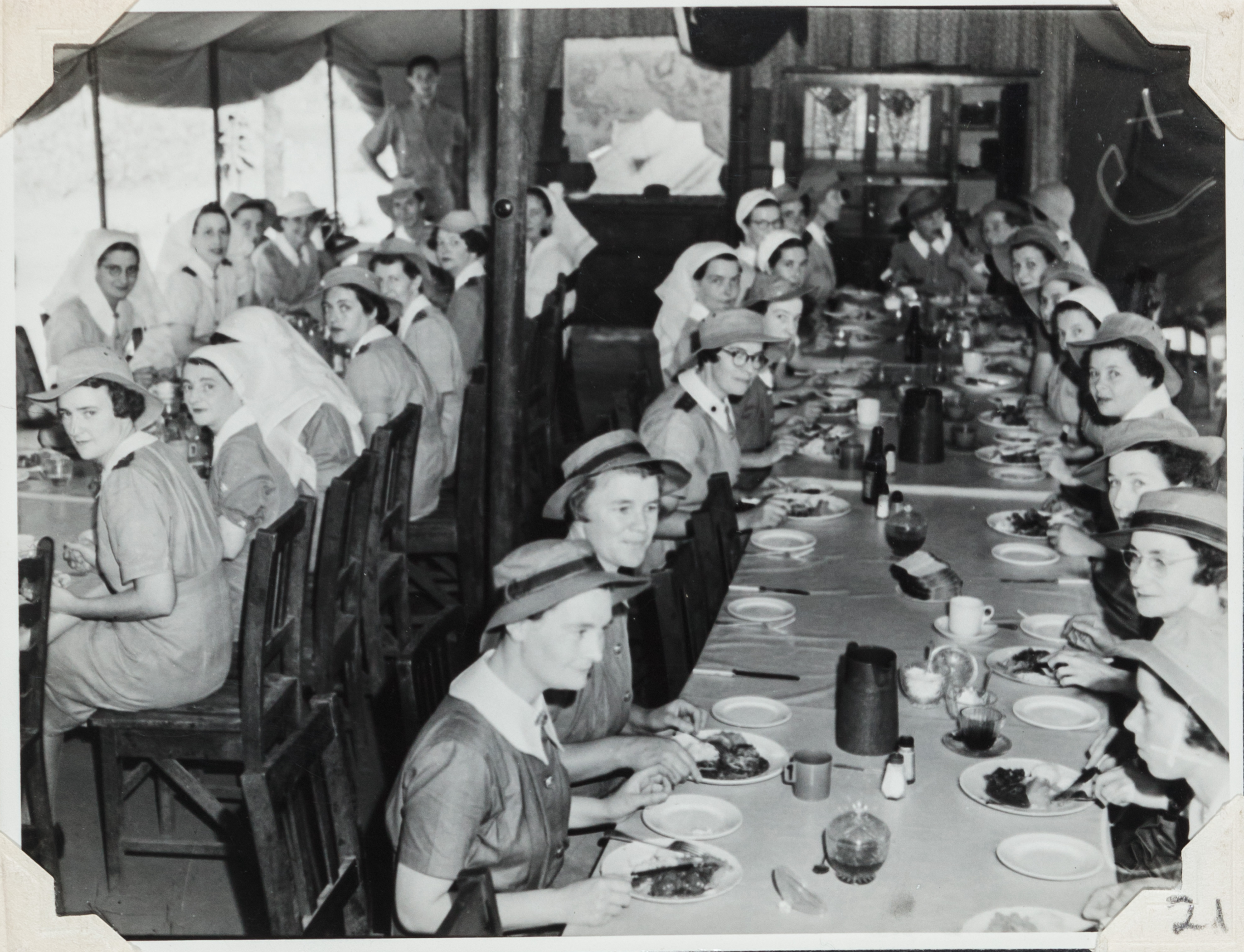 n Sisters Mess. Five large tables placed end to end with nurses seated around and eating a meal together.