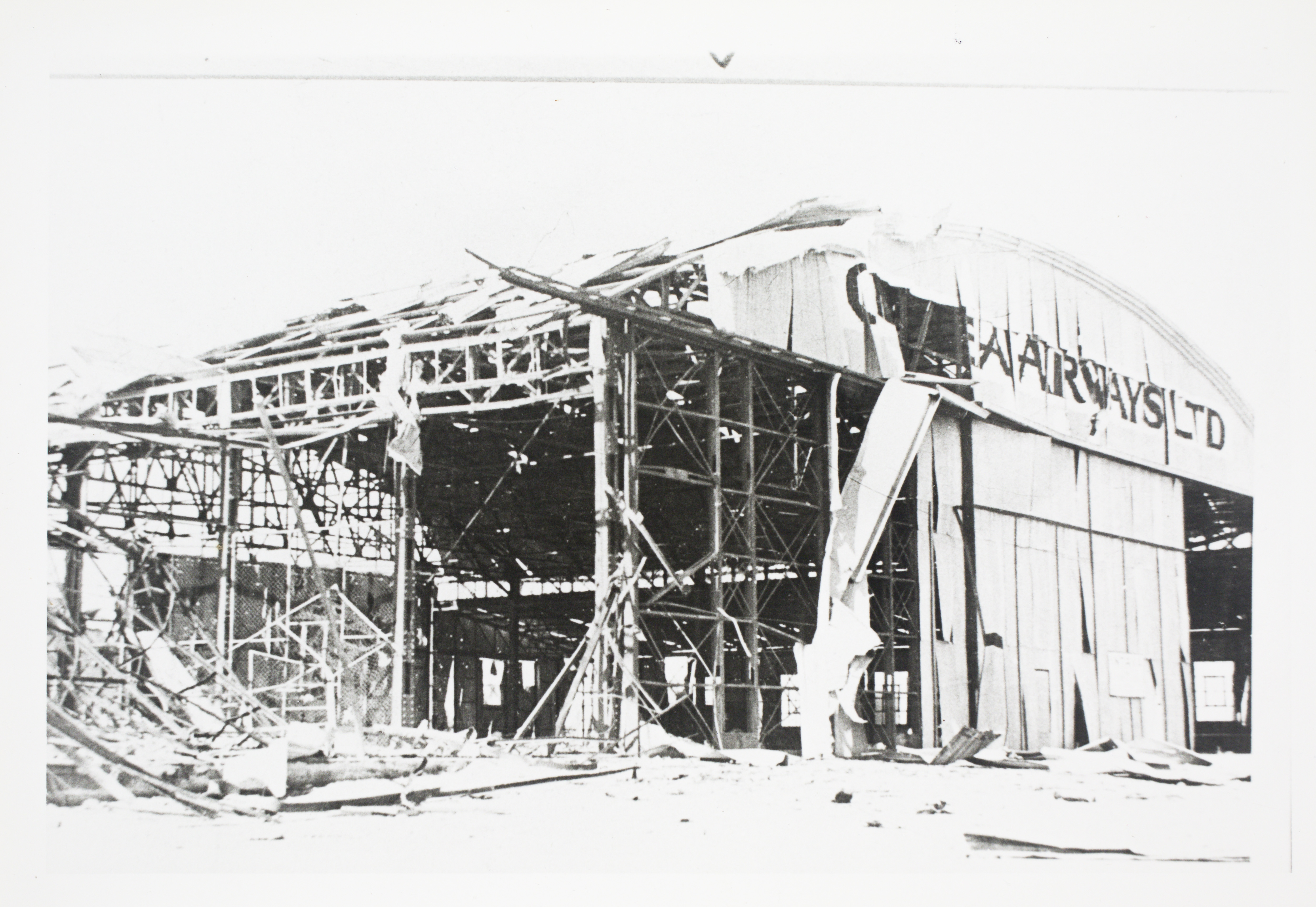 Bombed Guinea Airways hangar on civil strip at the Darwin Aerodrome after the first day of bombing.