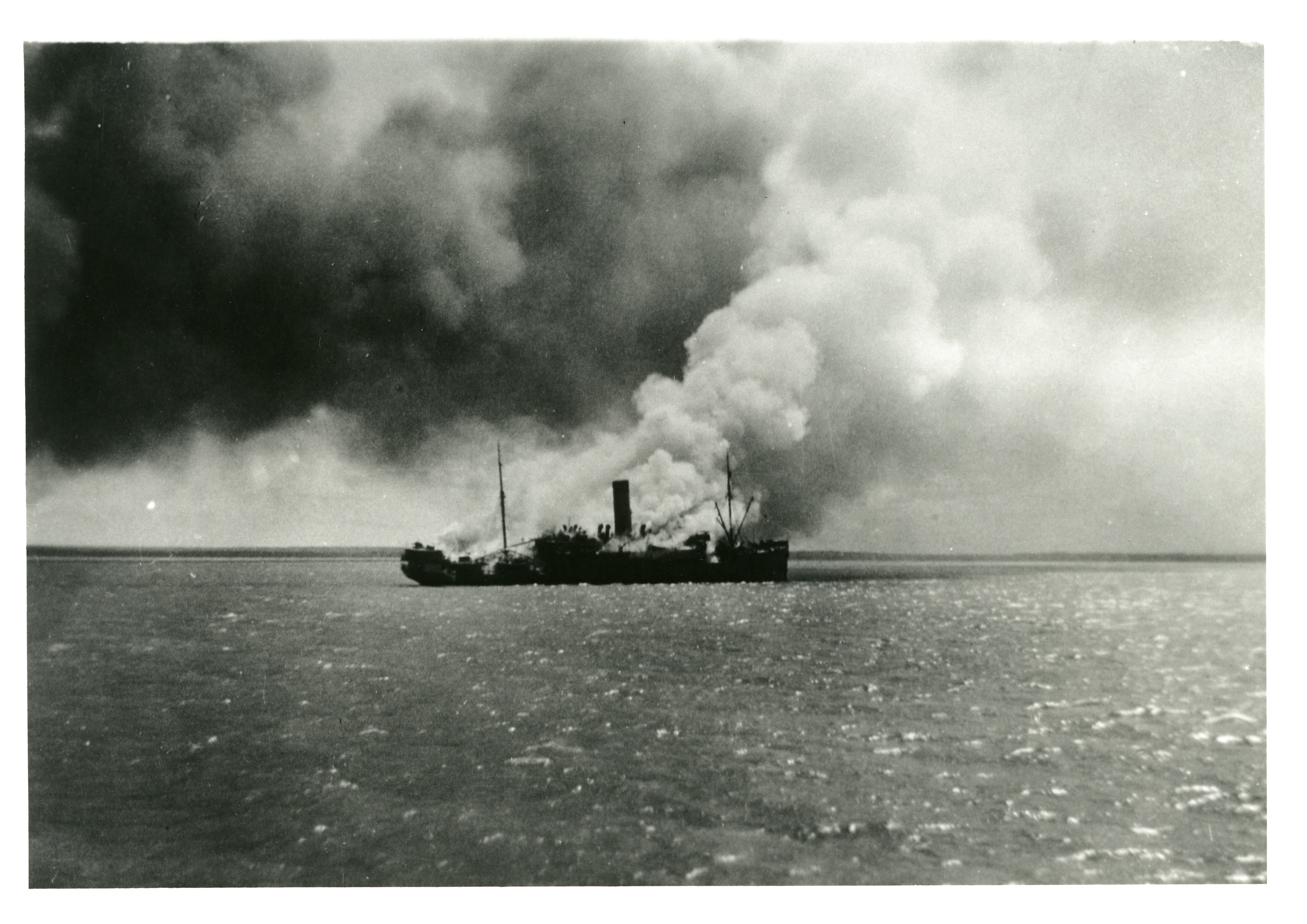 HMAT Zealandia burning on Darwin Harbour during the first raid