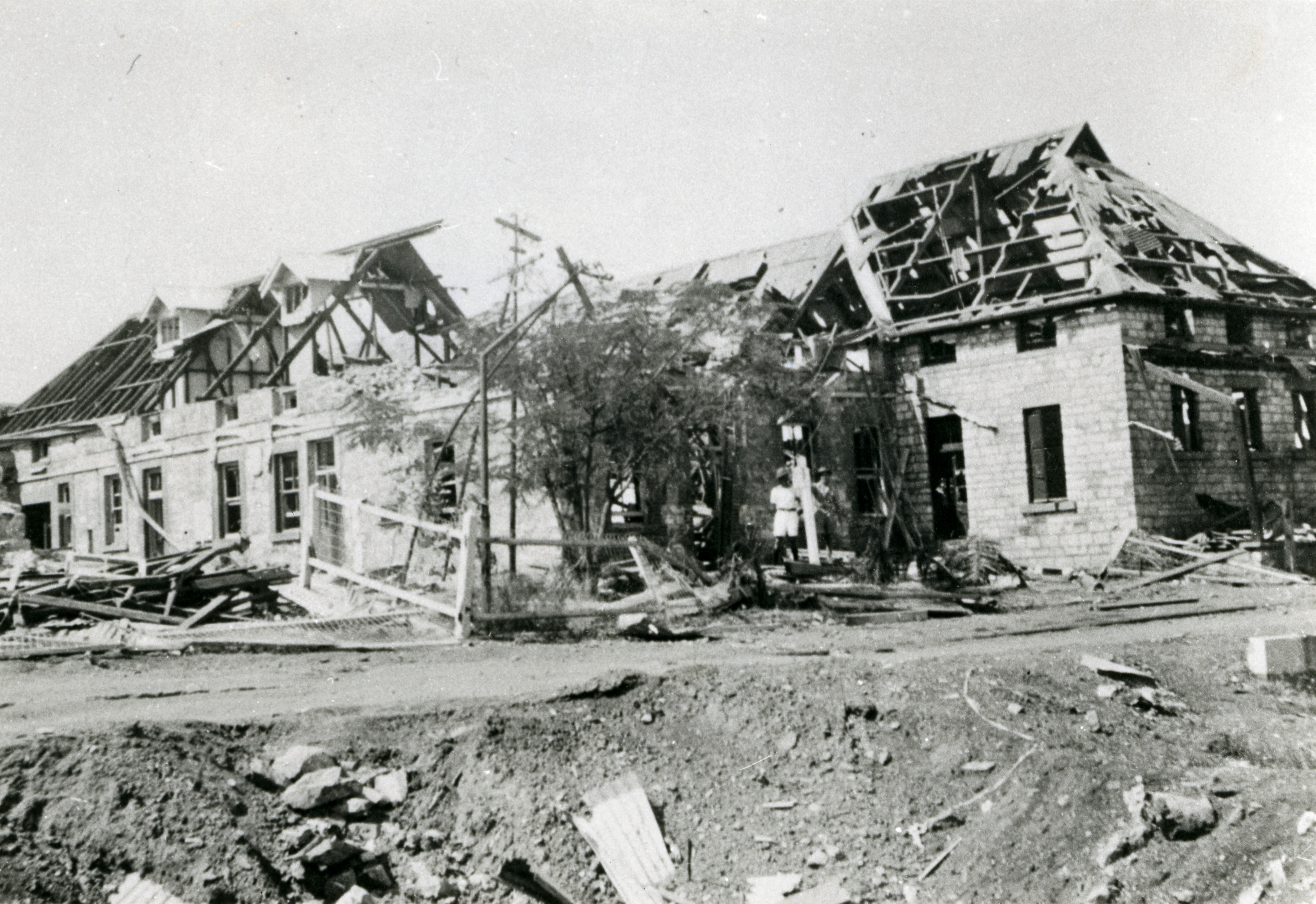 Parts of BAT, cable station, telegraph offices and Darwin Post Office buildings destroyed in the first Japanese air raids on 19 February 1942, showing one of the bomb craters in the foreground.