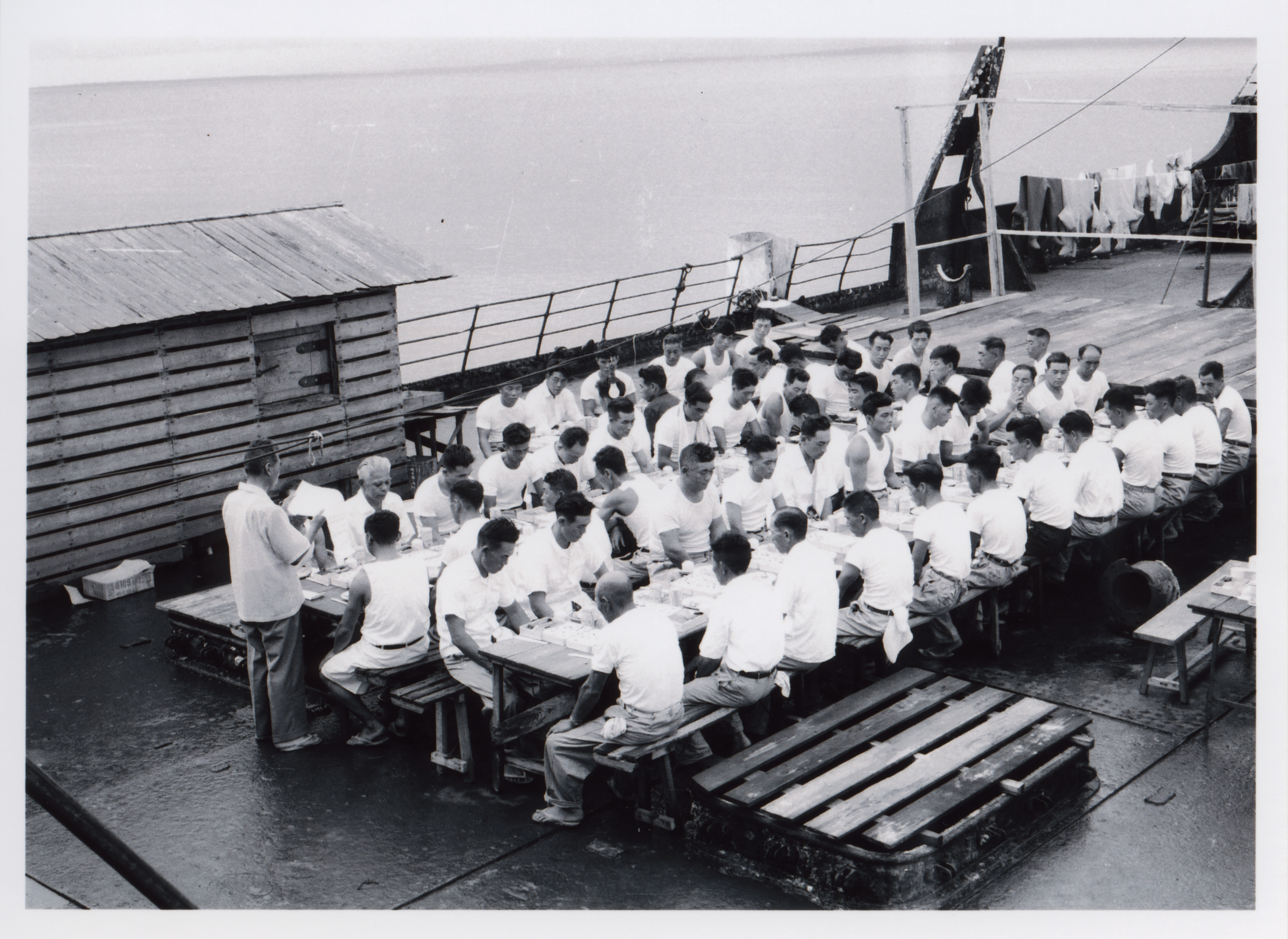 Employees of the Fujita Salvage Company celebrate a New Year's Day lunch on board the MV British Motorist in 1961.