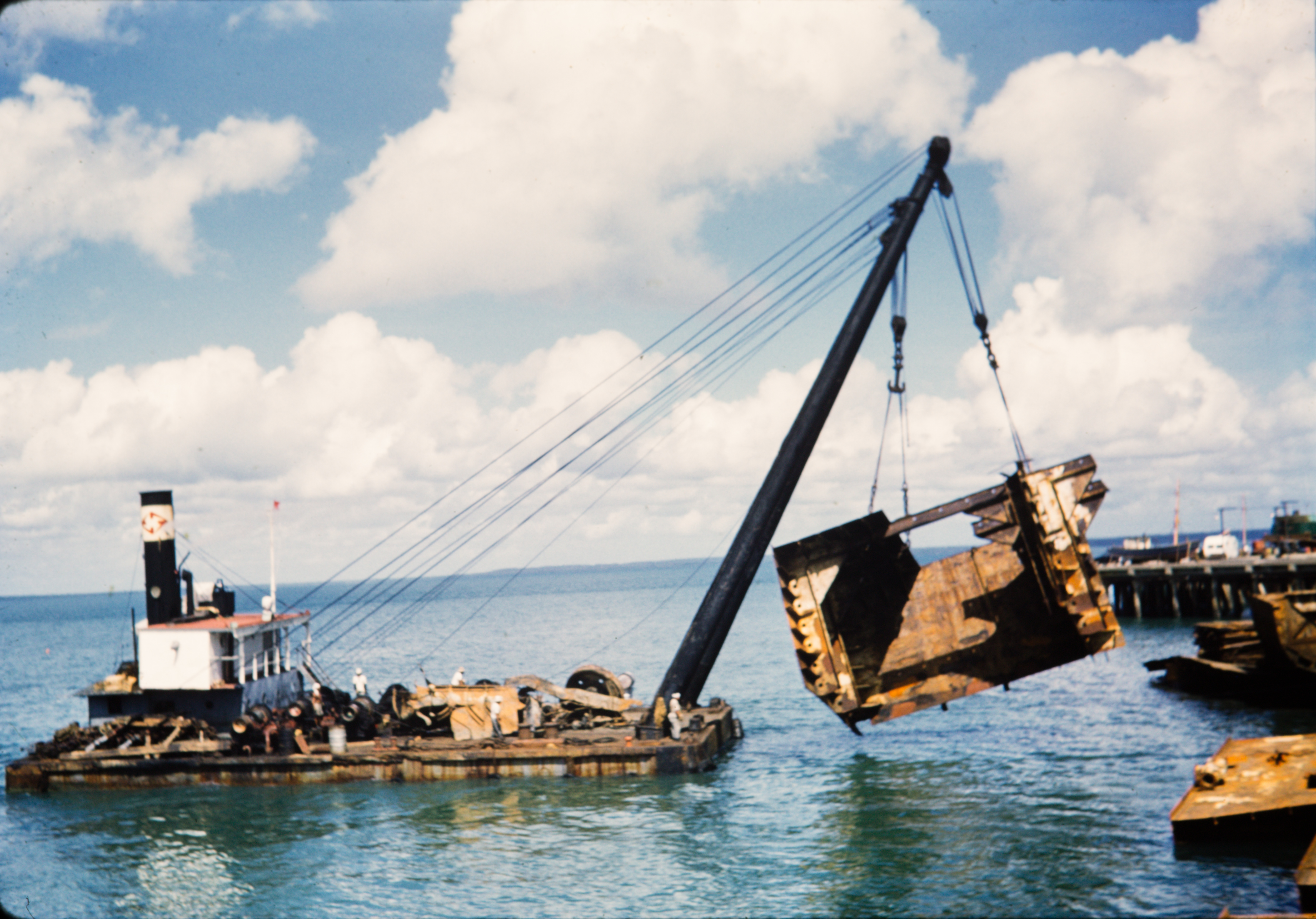 A floating barge crane raises salvage material from Darwin Harbour.