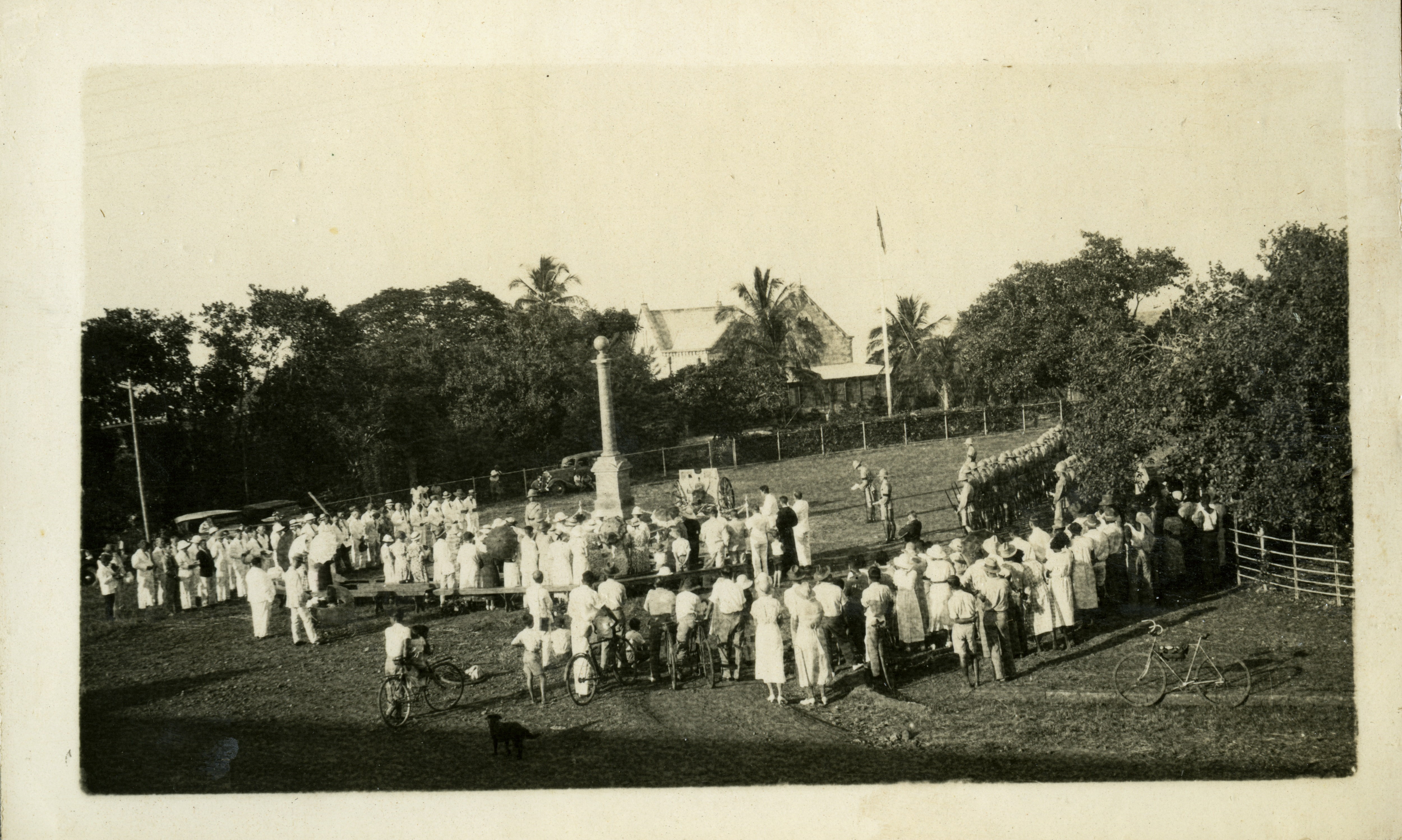 A large crowd of men and women surround the Cenotaph at centre. At far right is a line of troops, the Darwin Garrison. In the background is Government House and a flagpole with flag. In the foreground at right is a pushbike.