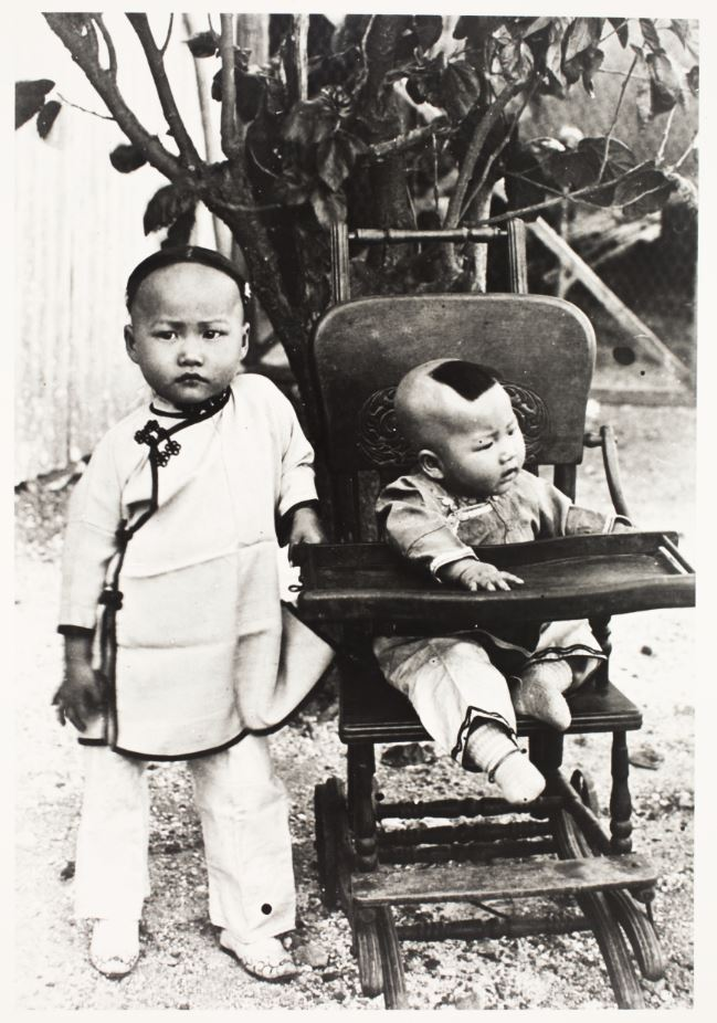 Black and white photo. A young child and a baby. The baby is seated in a wooden pushchair
