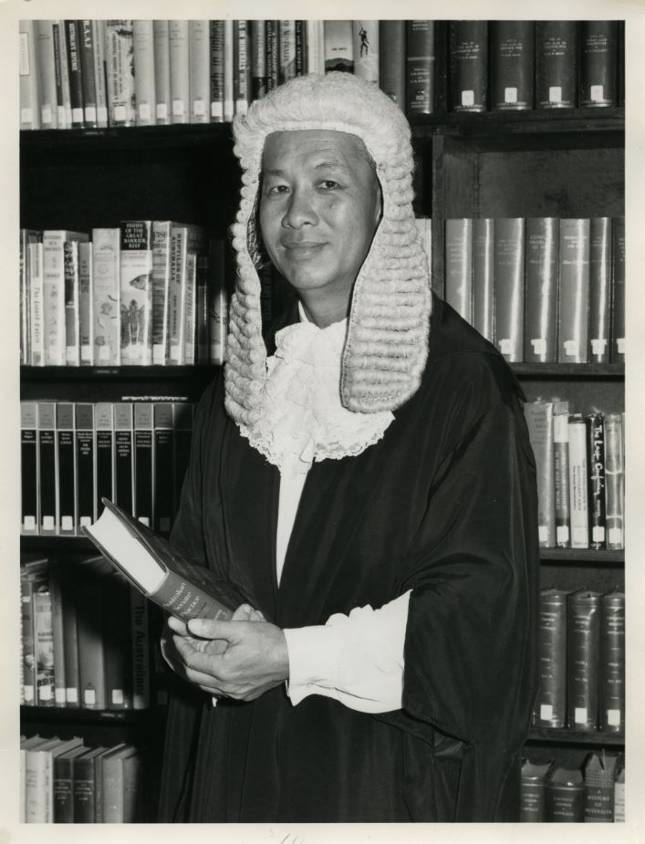 Black and white photo. Man in court wig and gown standing in front of a bookcase and holding a book.