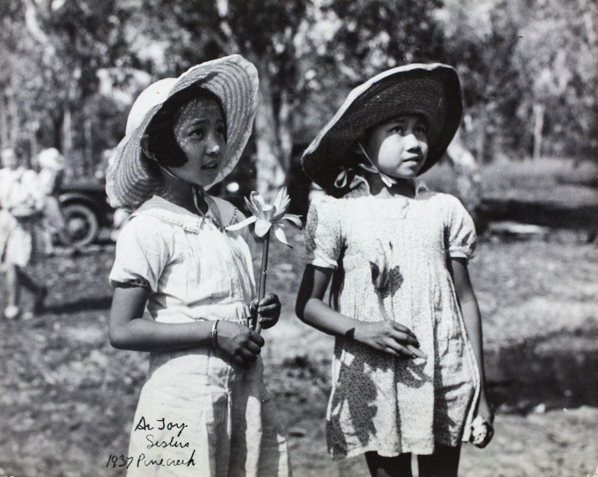 Black and white photo. two girls wearing sunhats and holding water lilies